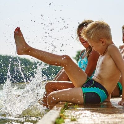 things to do in the summer, family sitting on dock by water