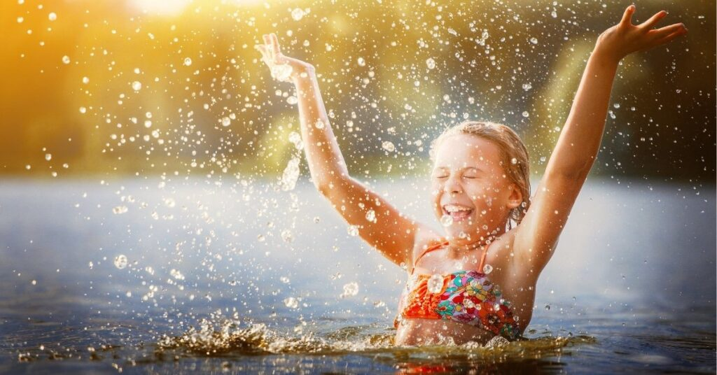 girl playing in water, free and cheap things to do in the summer with kids