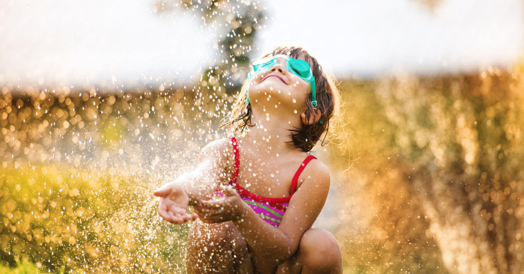 girl playing in a sprinkler
