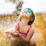 girl playing in a sprinkler