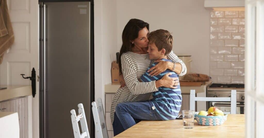 mother meeting her son's emotional needs by giving him a hug